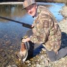 Norm Elliott, of rural Victoria, Australia, kneels by the Mataura River with one of the ducks he...