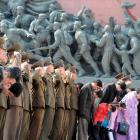 North Korean soldiers salute as civilians bow to bronze statues of North Korea's late founder Kim...