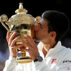 Novak Djokovic kisses the trophy after beating Roger Federer in their men's singles final at...