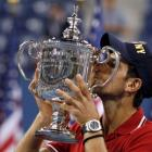Novak Djokovic of Serbia kisses his trophy after defeating Rafael Nadal of Spain in the men's...