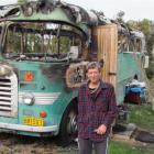 Oamaru man Colin Hitchcox beside his house bus which was destroyed by fire early yesterday...