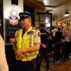 Sergeant Ian Paulin, of  Dunedin, talks to a bar patron in the Octagon on Saturday night. Photos ...