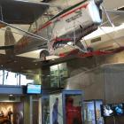 An Auster ZK BDX skiplane hangs above a display of the down bodysuit, ice axe and gloves used by...