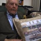 Waimate centenarian Jim Brown with the cushion presented to him by the Waimate Dog Trial Club....