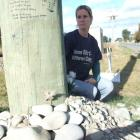 Debbie Devon sits at the site of a car crash at Waitaki Bridge which claimed the lives of her...