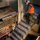 One of the last flights of stairs is hoisted to the top of the stairwell for removal from the...