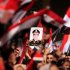 Opponents of Egyptian President Mohamed Mursi hold a poster featuring the head of Egypt's armed...
