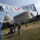 """Opponents of the health care reform bill carry a """"Kill the Bill"""" sign as protesters begin to..."""