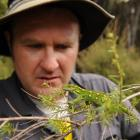 Orokonui Ecosanctuary conservation manager Elton Smith prepares to release a jewelled gecko at...