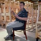 Otago Furniture supervisor Ron St Clair-Newman tests the Middlemarch dining chair he designed...