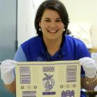 Otago Museum marketing officer Kimberley Smith holds an embroidery sampler made by Ngaere...
