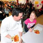 Otago Polytechnic cookery senior lecturer Adrian Woodhouse serves Forbury School pupil Ashleigh...