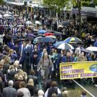 Otago Polytechnic graduands walk through central Dunedin, watched by friends, family members and...