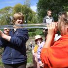 Otago Regional Council land resources manager Susie McKeague shows Maddi Halcrow (12) how to use...