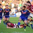 Otago's Fetu'u Vainikolo attempts an offload to fellow winger Ryan Shortland (left) as he is...