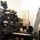 Otakou Press printer in residence Peter Vangioni works on the Columbian Eagle press in the...