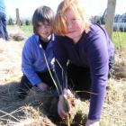 Otama School pupils Laura Whyte (7, left) and Ruby Holz (10) plant a tree on a riparian strip...
