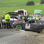 Paramedics (left) treat the driver beside his crashed car where it came to rest after hitting a...