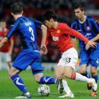 Otelul Galati's Cornel Rapa (L) and Loan Filip challenge Manchester United's Park Ji-sung during...