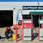 Outram Garage  owner-operator Ray Warnoch, who fills  a jerry can for a customer as his dog Tess...