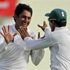 Pakistan spinner Saeed Ajmal, left, is congratulated by teammate Umar Akmal after bowling out...