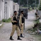 Pakistani army troops guard the perimeter of the walled compound of a house where Osama bin Laden...