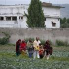 Pakistani family members leave the area after viewing the walled compound of a house, seen in...