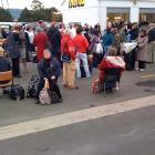 Passengers outside Dunedin Airport after they were evacuated this morning. Photo by Craig Baxter