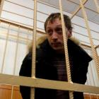 Pavel Dmitrichenko looks out from the defendant's holding cell during a court hearing in Moscow....
