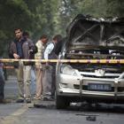 People examine a damaged Israeli embassy car after an explosion in New Delhi. REUTERS/Parivartan...