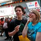 People gather outside the NASDAQ Marketsite waiting to see Facebook's share prices posted inside...