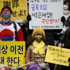 People hold placards next to a statue symbolising ''comfort women'' during a weekly anti-Japan...