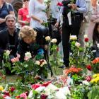 People lay flowers outside the cathedral in Oslo on the anniversary of the twin Oslo-Utoeya...