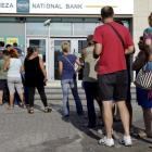 People line up to withdraw cash from an ATM at a bank on the island of Crete. REUTERS/Stefanos...