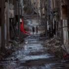 People run down a street in Deir al-Zor, Syria. REUTERS/Khalil Ashawi