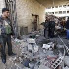 People stand at the site of a suicide bombing in Damascus, Syria. (AP Photo/Muzaffar Salman)