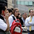 People talk on cellphones after being evacuated from their buildings following an earthquake in...