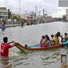 People travel on a boat as they move to safer places through a flooded road in Chennai, India....