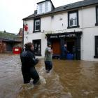 People wade through a flooded street in Dumfries, Scotland. REUTERS/Darren Staples