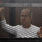 Peter Greste stands in a metal cage during his trial in a court in Cairo in March last year....
