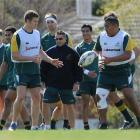 Phil Kite (centre) passes the ball to team-mate Lindsay Crook as skills coach Andy Clark (wearing...