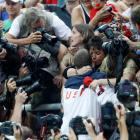 Photographers surround Michael and Debbie Phelps, centre, and his sister Whitney Flickinger,...