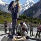 Phurenje and Edmund Sherpa lay a wreath at the base of a statue of Sir Edmund Hillary at Aoraki...