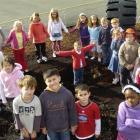 Beryn Abbott (7) surrounded by her Mornington School, Dunedin, classmates, stands in the black...
