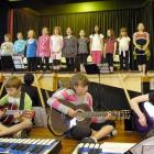 Playing guitars in front (from left) are William Archer (11), Ben Rekittke (10), Eliza Booth (11)...
