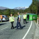Police and ambulance staff inspect the site of a crash on the Queenstown-Glenorchy road this...