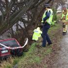Police and fire personnel inspect the site of a crash near ...