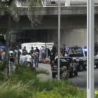 Police and members of a forensic team stand around bodies on a motorway in Boca del Rio, on the...
