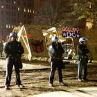 Police cordon off the area as workers take down a wooden structure erected by Occupy DC...