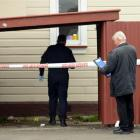 Police examine the scene of an alleged sexual assault at a South Dunedin property yesterday...
